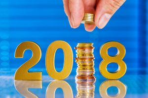 hand push the euro coin in to 2018